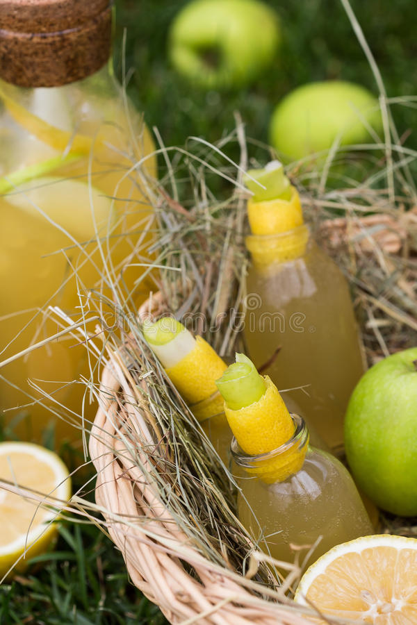 Refreshing lemonade with apple and lemon in a picnic basket. Cold summer drinks in garden. stock photos