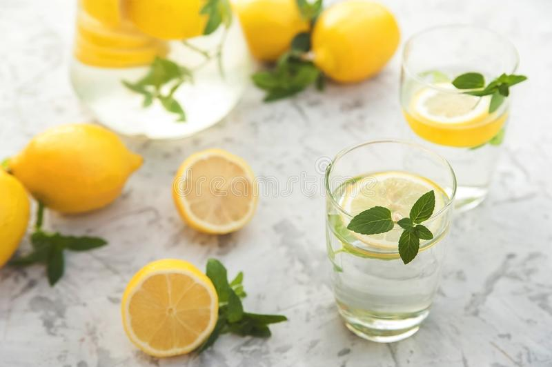 Refreshing lemonade with lemons, mint in a transparent jug and glasses on a light concrete background close-up. Background and pla stock image