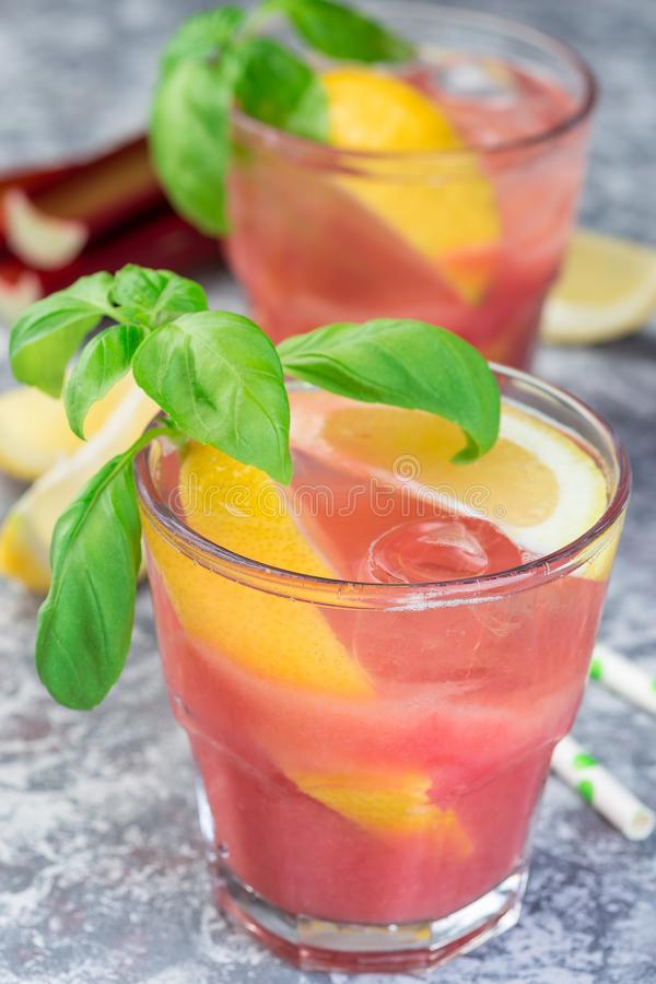 Refreshing lemonade with rhubarb, lemon, sparkling water and basil in a glass, vertical, closeup royalty free stock photos