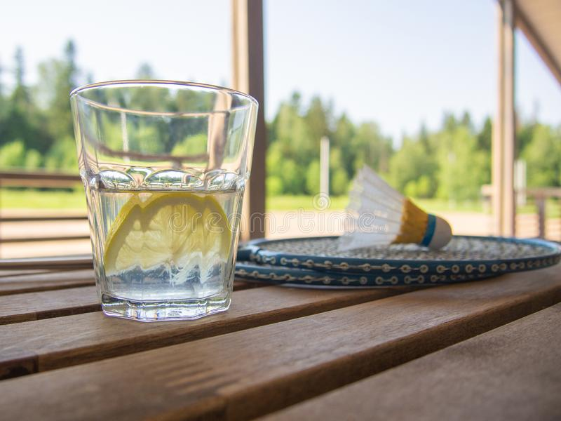 Refreshing lemonade with a slice of lemon in the foreground. Two badminton rackets and shuttlecock on wooden table. Lush green. Foliage. Wooden country royalty free stock images