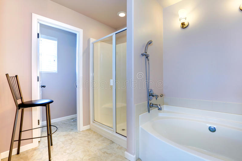 Refreshing light lavender bathroom with white bath tub and shower stock photos
