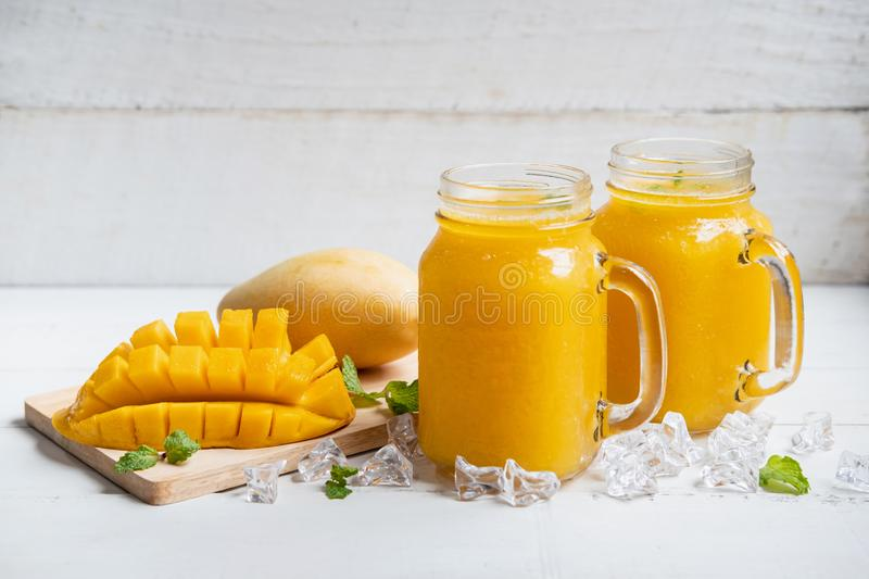 Refreshing mango smoothies in glass with ripe mango. On white wooden table royalty free stock images