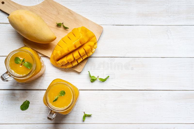 Refreshing mango smoothies in glass with ripe mango on white wooden table and copy space. Top view stock photo