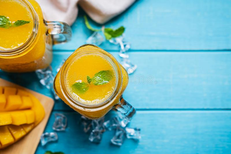 Refreshing mango smoothies in glass with ripe mango on wooden table and copy space. Top view royalty free stock photos