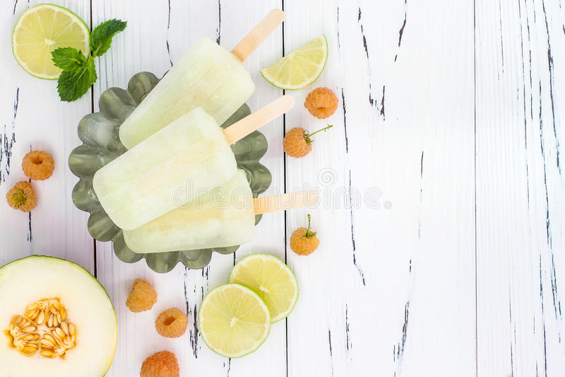 Refreshing mexican style ice pops - raspberry, lime, honeydew margarita paletas - popsicles. Top view. Cinco de Mayo recipe. Refreshing mexican style ice pops royalty free stock image
