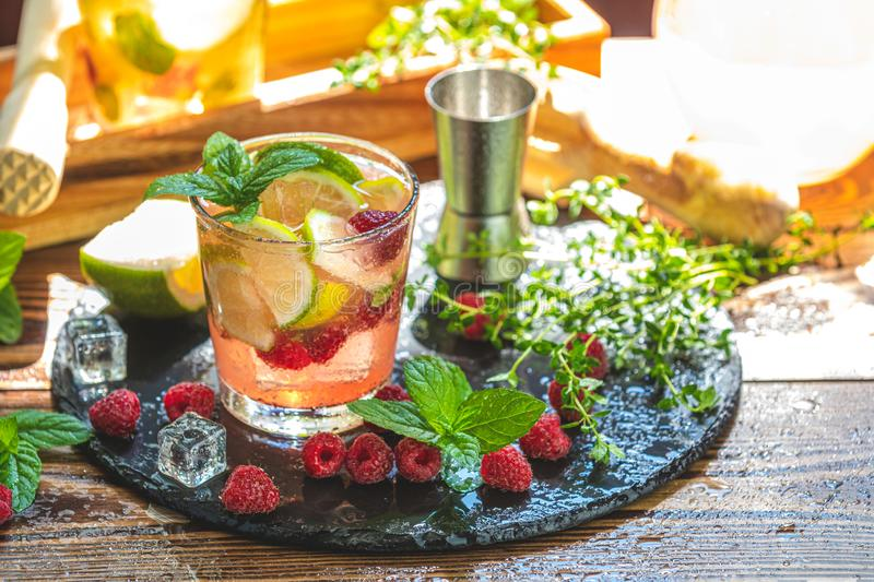 Refreshing mint cocktail mojito with rum, lime and raspberry, cold drink or beverage stock photos