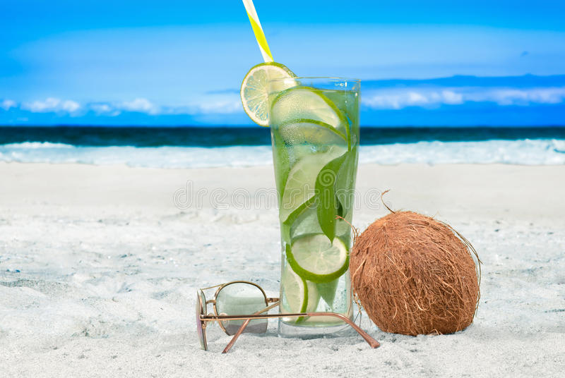 Refreshing Mojito drink and coconut on the beach stock photos