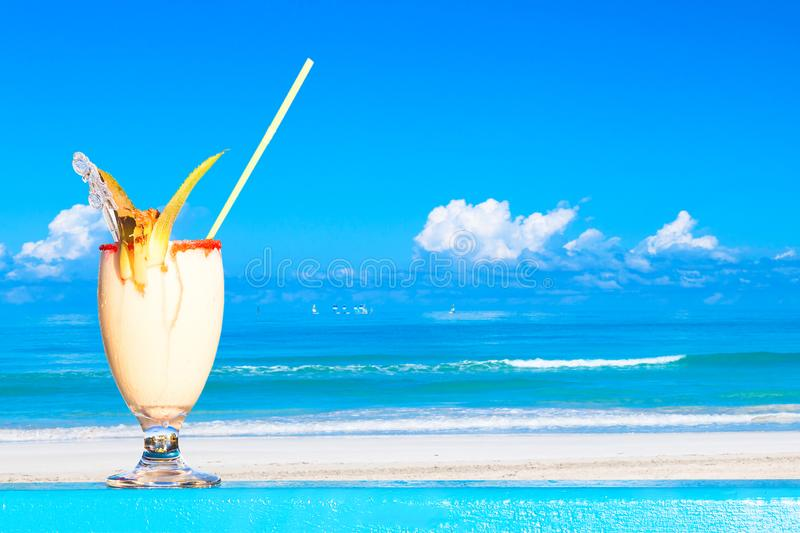 Refreshing pina colada cocktail against water oceam and amazing beach background. Summer vacation concept royalty free stock image