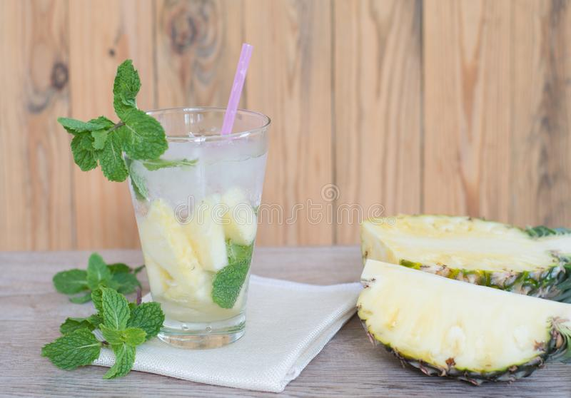 Refreshing pineapple lemonade soda soft drinks. Or energy drink with ice in a clear tall glass on wooden background stock photography