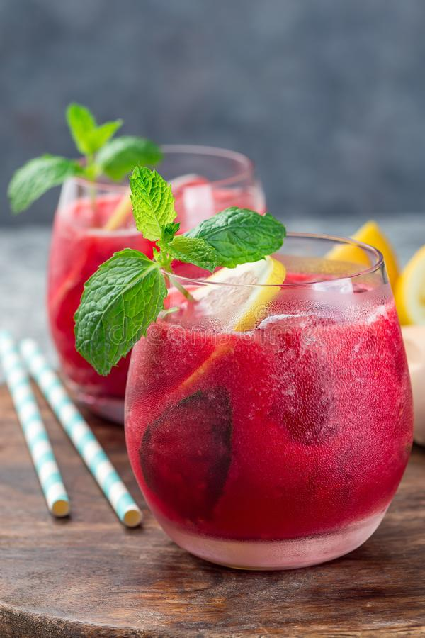 Refreshing raspberry, lemon and mint lemonade with sparkling water in a glass, vertical royalty free stock image