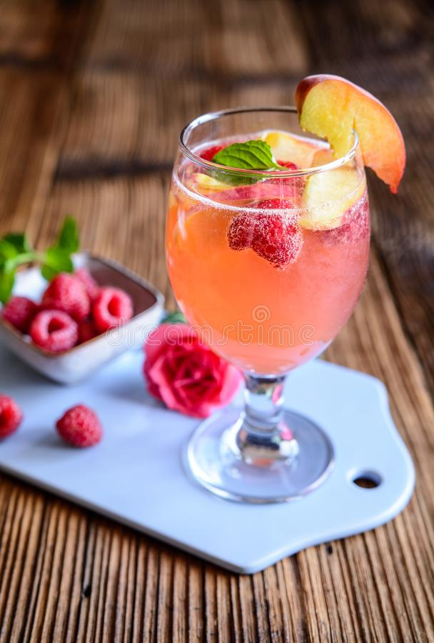 Delicious raspberry peach mimosa drink on a wooden background royalty free stock photography