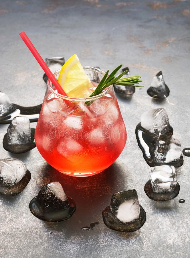 A refreshing red drink with ice, lemon and rosemary.Aperitif with campari stock photo