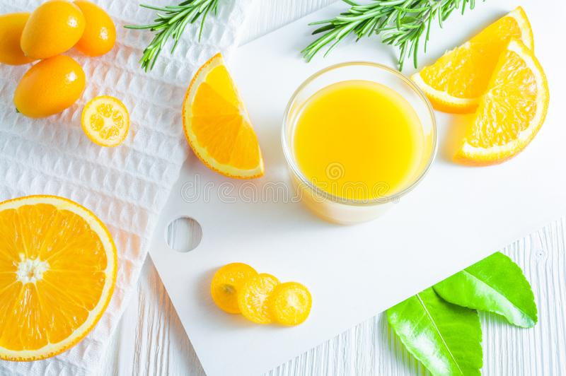 Refreshing summer citrus drink with orange, kumquat and rosemary. White background, flat-lay, top view royalty free stock photography