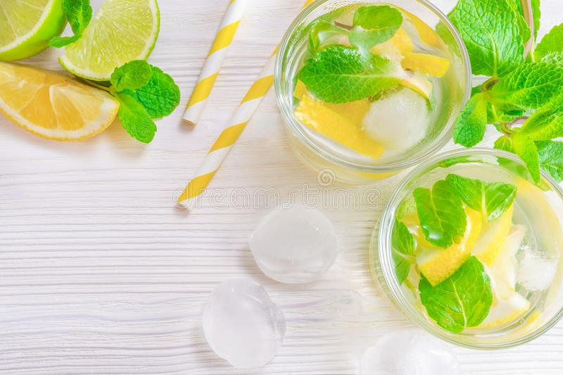 Refreshing summer drink mojito with lime, lemon and mint, with ice cubes on white wooden background. Flat-lay, top view. Two glasses with summer drink of lemon royalty free stock photography