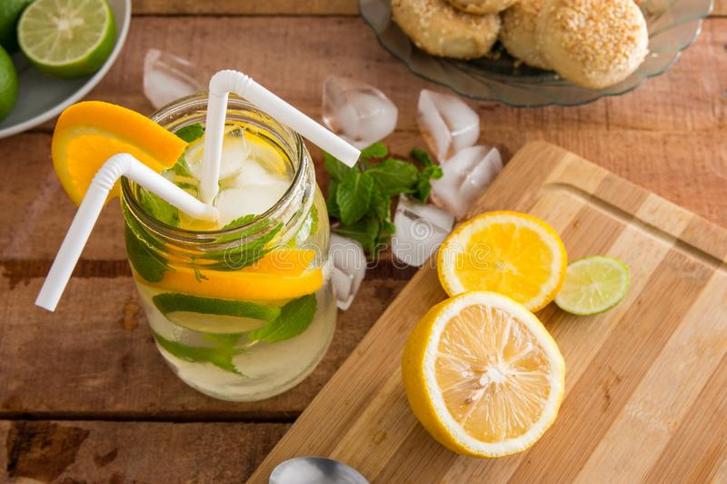 Refreshing summer fruit drink with orange, lemon and mint on wooden benchtop royalty free stock photos