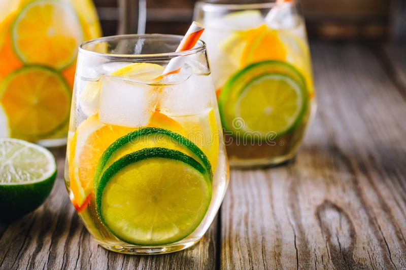 A refreshing summer ice-cold drink. White wine sangria in glass with lime, lemon and orange. On a wooden rustic background stock photo