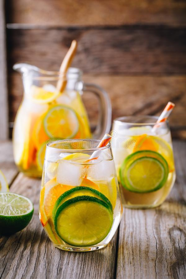 A refreshing summer ice-cold drink. White wine sangria in glass with lime, lemon and orange. On a wooden rustic background stock photos