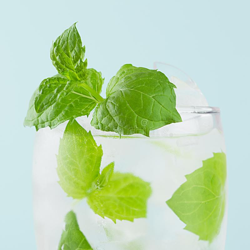 Refreshing summer mint water with green leaf, ice cubes, tonic in light soft pastel blue color background, closeup, top, half. Refreshing summer mint water with royalty free stock photos