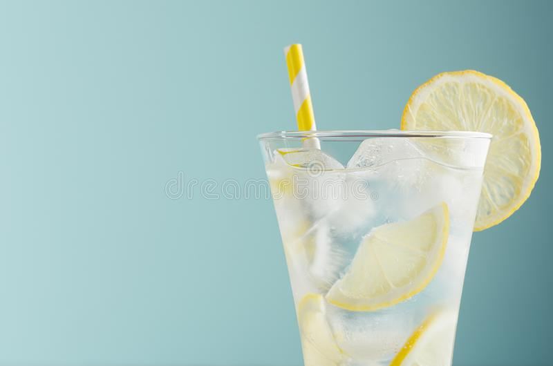Refreshing summer tonic water with lemon, ice cubes, yellow straw in light soft pastel blue color background, closeup, half, top. Refreshing summer tonic water stock photos