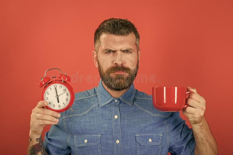 Refreshment break and energy. Guy with mulled wine, clock on red background. Red mug with alarm, perfect morning. Man drink morning coffee or tea with alarm stock image