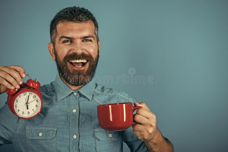 Refreshment break and energy. hipster with milk cup, time, copy space. Refreshment break and energy. hipster with milk cup, time. Man drink morning coffee or tea royalty free stock images