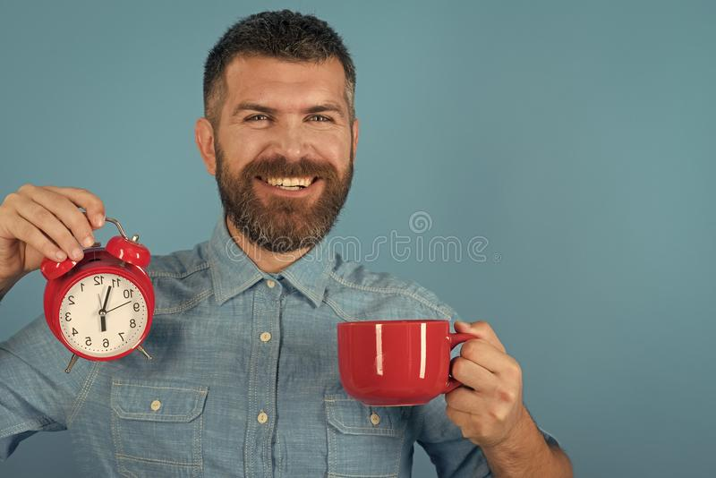 Refreshment break and energy. Red mug with alarm, perfect morning, copy space. Refreshment break and energy. Red mug with alarm, perfect morning. Man drink stock photography