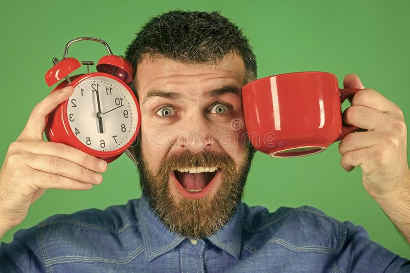 Refreshment break and energy. Hipster with milk cup, time. Happy guy with mulled wine, clock on green background. Red mug with alarm, perfect morning. Man stock photography