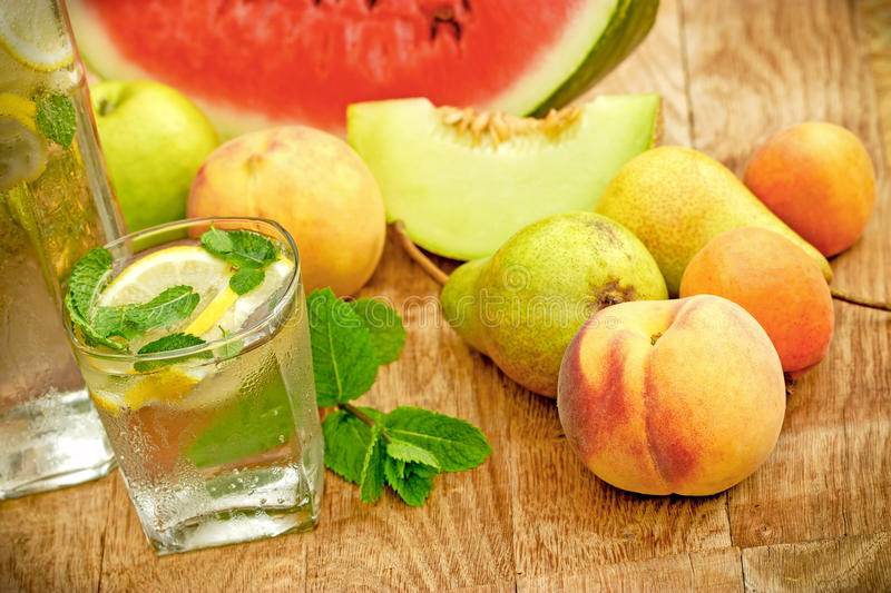 Refreshment in hot days of summer - fruit juice and fresh organic fruits. On table stock photography
