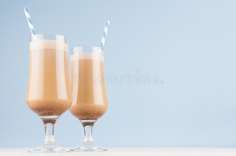 Refreshment morning cappuccino coffee in two exquisite transparent glass with foam and striped straw in light blue interior. Refreshment morning cappuccino stock photos