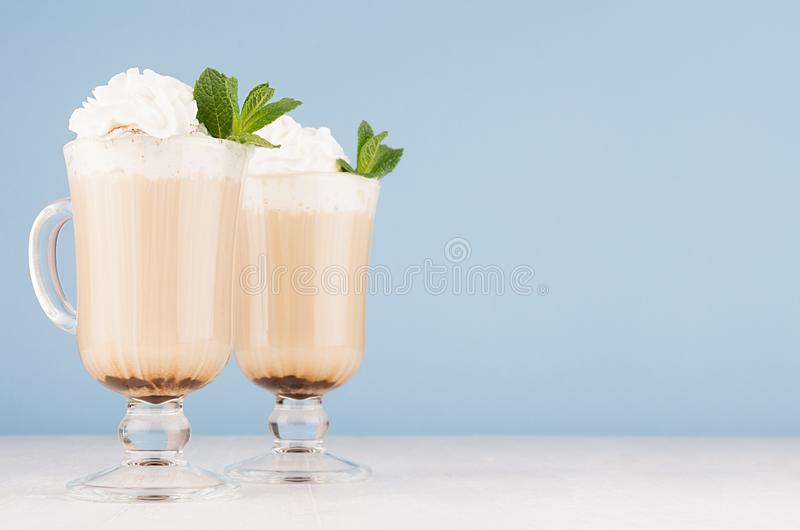 Refreshment morning cappuccino coffee with whipped cream and green mint in two exquisite transparent glass in light blue interior. Refreshment morning royalty free stock image