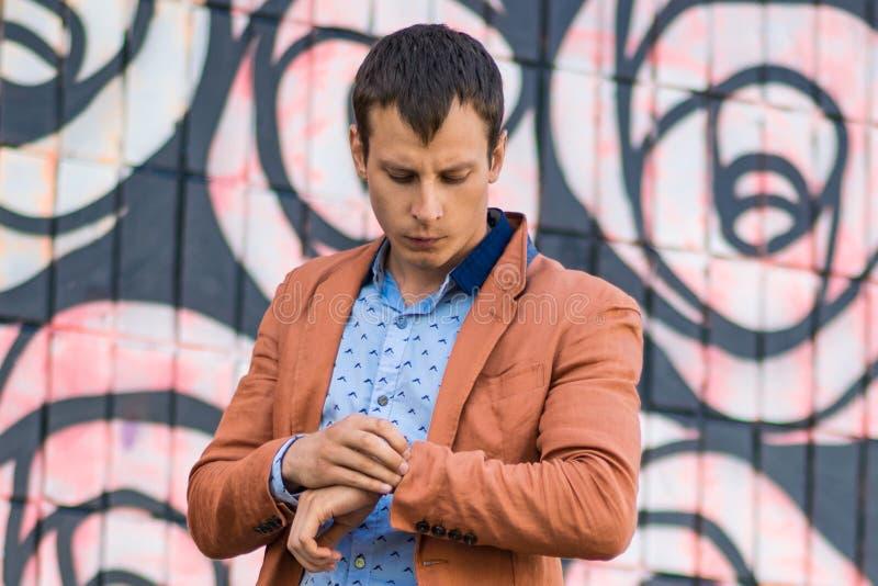 Refresque al hombre de la moda en la camisa azul que se coloca y que mira lejos foto de archivo