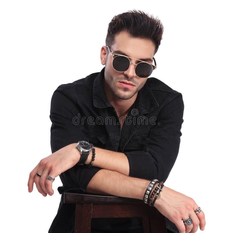 Refresque al hombre joven en la ropa negra que descansa codos en silla imágenes de archivo libres de regalías