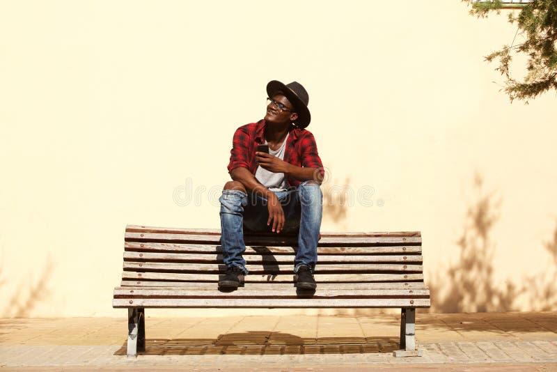 Refresque al individuo africano en el sombrero que se sienta en banco por la calle fotos de archivo