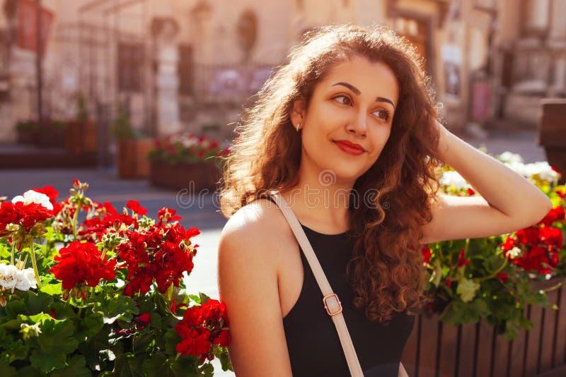 Refrigeração bonita feliz da mulher cercada por flores Retrato exterior da universitária de sorriso na rua do verão fotos de stock royalty free