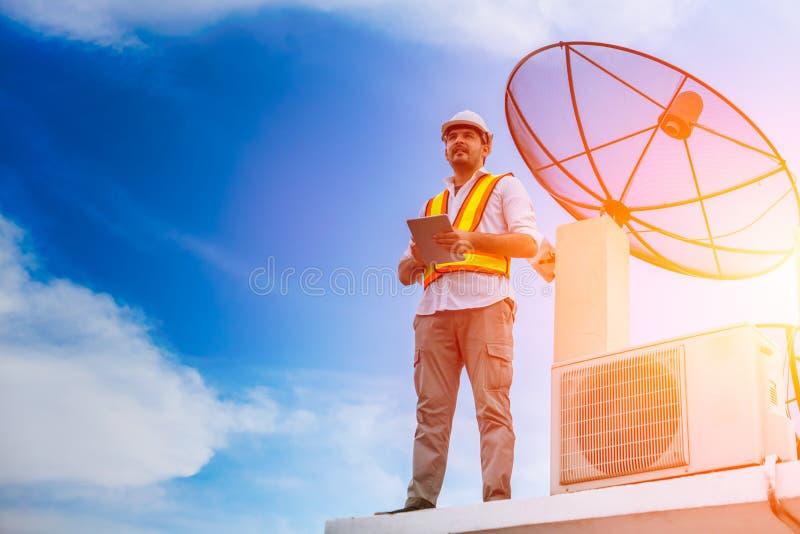 Refrigerador e antena parabólica do ar do reparo do trabalhador manual fotografia de stock