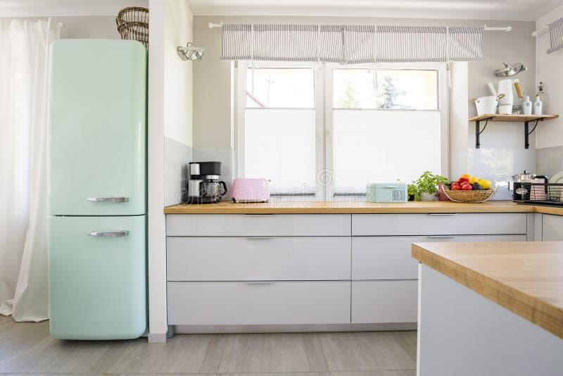 Refrigerador neo de la menta que se coloca en foto real del interio brillante de la cocina foto de archivo