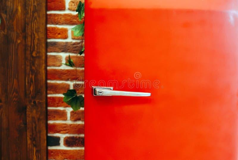 Refrigerador vermelho do estilo retro do vintage contra o fundo da parede de tijolo fotos de stock royalty free