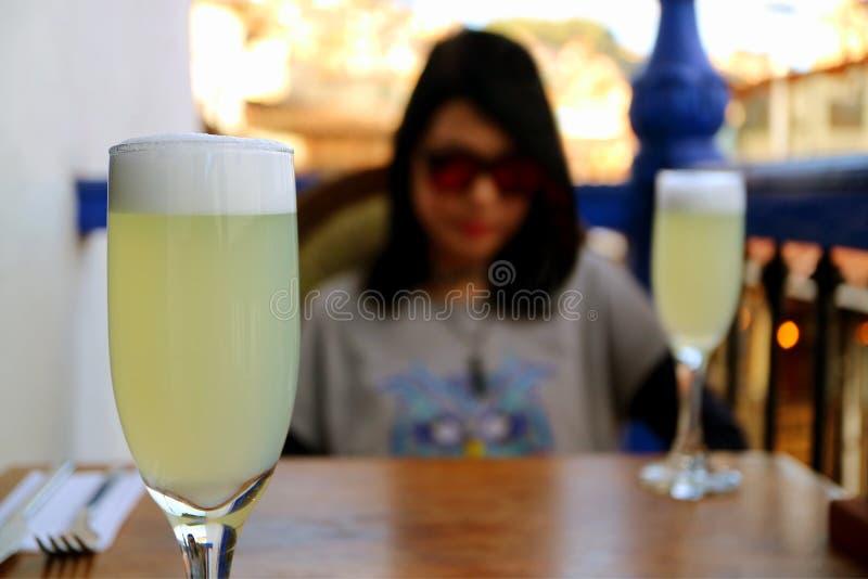 Refrigerando para fora com o cocktail ácido peruano de Pisco do agridoce, fêmea de relaxamento borrada no fundo fotografia de stock royalty free