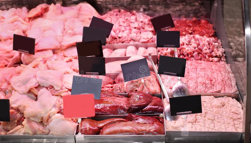 Refrigerated display case with fresh meat in butcher shop stock image