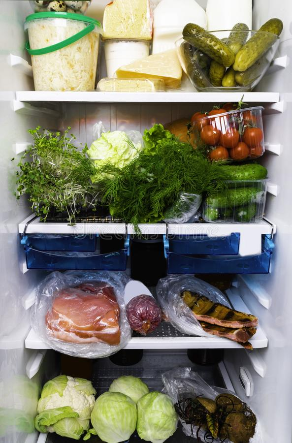 Refrigerator full of assorted food ingredients, vegetables, meat and dairy products close up health care, dieting concept royalty free stock image