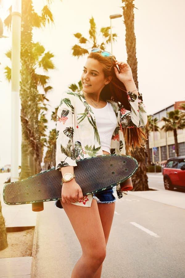 Refrigere a mulher na moda que levanta com sua placa longa durante o passeio da recreação no verão imagem de stock