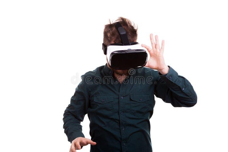 Refrigere o homem novo que experimenta a realidade virtual através de uns auriculares de VR fotos de stock
