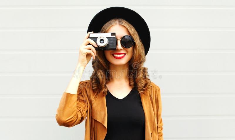 Refrigere o modelo engraçado da menina com a câmera retro do filme que veste um chapéu elegante, revestimento marrom fotografia de stock