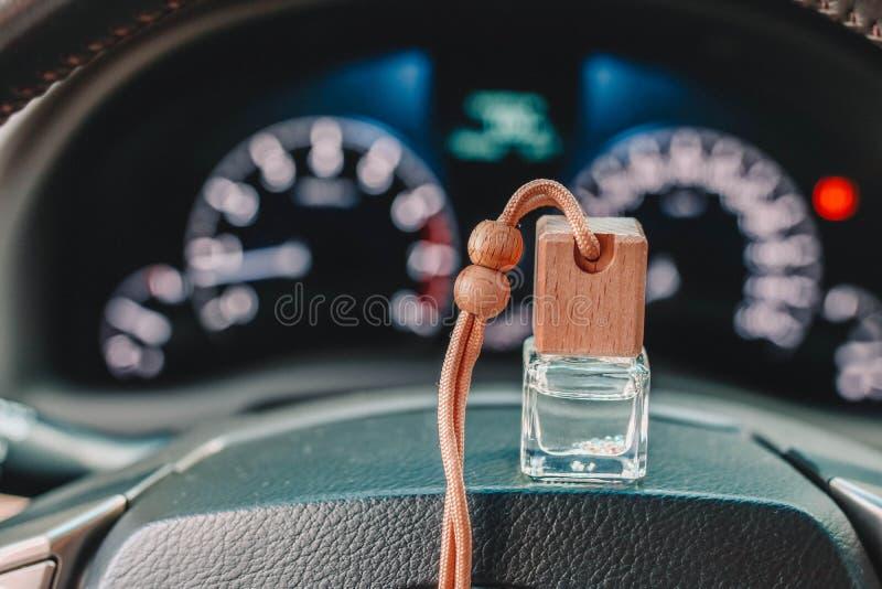 Refrogerador do perfume ou de ar do carro no volante e nas luzes de painel borradas no fundo fotografia de stock royalty free