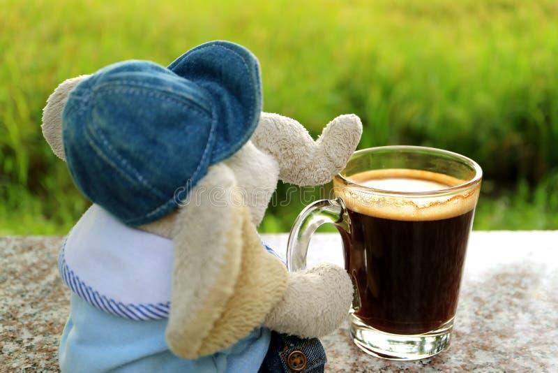 Refroidissez avec une tasse de café, une poupée d'éléphant avec du café chaud à la terrasse images stock
