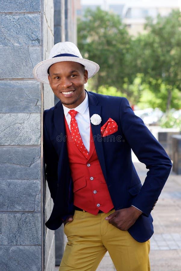 Refroidissez l'homme africain de mode dans le costume se penchant contre le mur photographie stock libre de droits