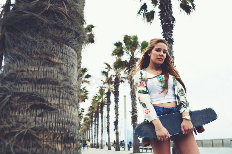 Refroidissez la femme à la mode posant avec son long conseil pendant la promenade de récréation en été photos stock