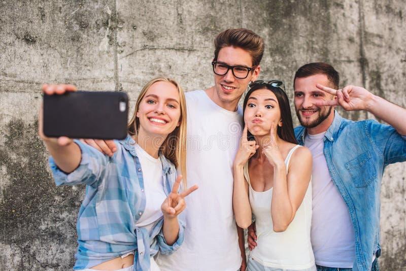 Refroidissez la photo de la société se tenant ensemble sur le fond gris La fille blonde prend le selfie de sa société Elle est photographie stock libre de droits