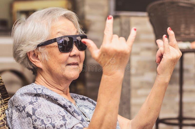 Refroidissez la vieille dame, utilisant des lunettes de soleil faisant le signe de roche image libre de droits