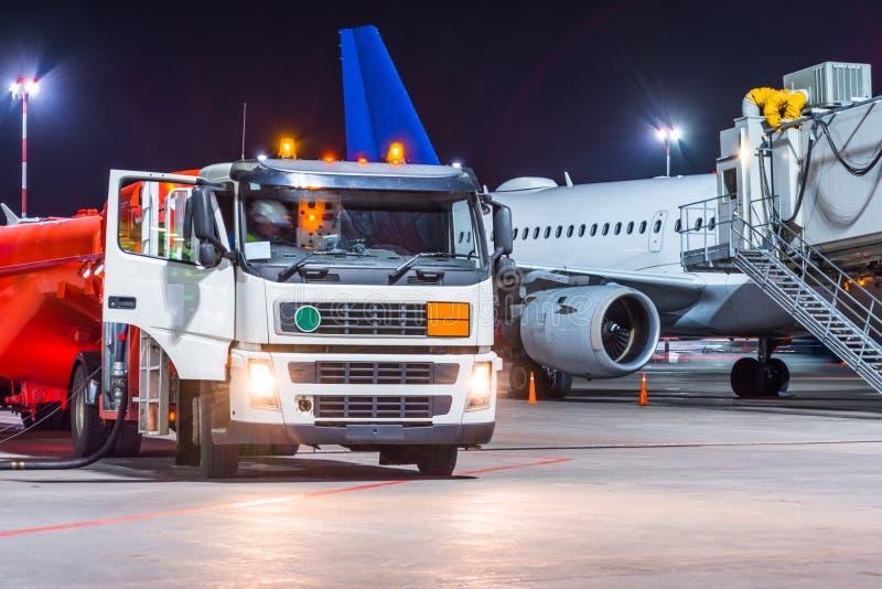 Refueling ciężarowy samolot, samolotu utrzymania paliwo przy lotniskiem przy nocą zdjęcia royalty free
